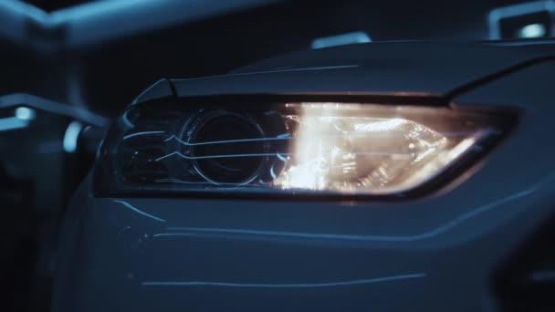 Detaily auta. Detailní záběr luxusní bílé kapoty s rozsvícenými světlomety. Výstražná světla. Koncept nových automobilů.