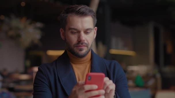 Šťastný mladý muž v nákupním centru s vánoční dárky v ruce používá Smartphone Dance. App Ikona s online transakcí. Finanční transakce v chytrém telefonu. Přijmout zprávu o navýšení peněz.
