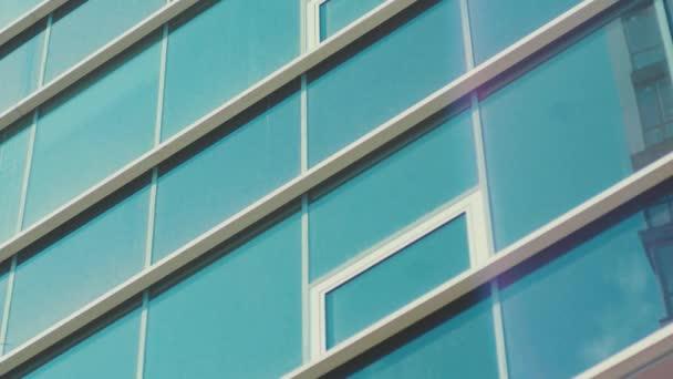 Skleněná průsvitná fasáda velké skleněné budovy. Sluneční erupce a modrá jasná obloha se odrážely v oknech. Kancelářská stavba. Centrum města.