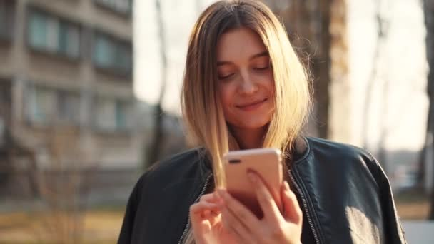 Attractive young woman in a bright sunlight uses phone standing in the city center look at camera smile girl shopping internet office technology outside using happy message mobile smartphone