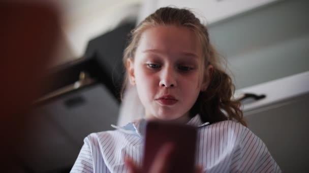 Portrét krásná mladá dívka používá smartphone v kuchyni jíst vážné doma dítě ruka domu žena internet tvář technologie slunce byt komunikace zpomalený pohyb