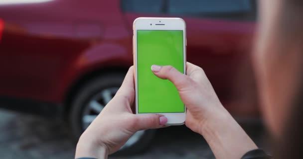 ÚJ YORK - Április 5, 2018: Közelkép kéz nő gazdaság használata fehér telefon zöld képernyős háttér piros autó görgetés oldalak lopás szörfözés internet technológia okostelefon chroma kulcs üzenet mobil