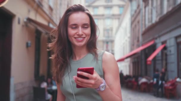 Close up smiling young woman in a bright sunlight uses red phone while walk in the city center summer internet business outside technology eye spring mobile slow motion street happy portrait