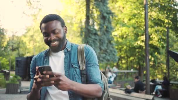 Glücklich afrikanischen amerikanischen jungen attraktiven Mann mit Telefon auf der Straße stehen Lächeln Sonnenlicht Sonnenuntergang Handy Computer Mode Internet Gesicht außerhalb Technologie Geschäftsleute schwarz junge Stadt Handy