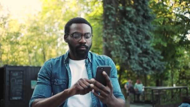 Porträt ernsthafte afrikanisch-amerikanische junge attraktive Mann mit Telefon steht auf der Straße Sonnenlicht Sonnenuntergang Handy Computer Mode Internet Gesicht außerhalb Technologie Geschäftsleute schwarz Stadt Handy