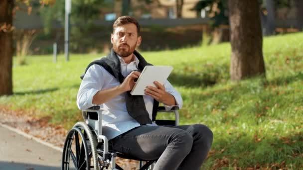 Schwerwiegender junger Mann im Rollstuhl mit Tablet-Computer im Park bei Sonnenlicht Behinderung Medizin. Möglichkeit behinderte Behinderte Tablet-Internet. Zeitlupe