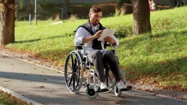 Attraktiver junger Mann im Rollstuhl mit Tablet-Computer im Park bei Sonnenlicht Behinderung Medizin. Möglichkeit behinderte Behinderte Tablet-Internet. Zeitlupe