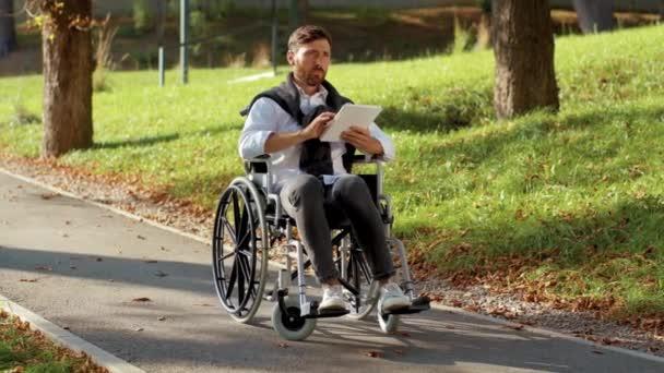 Nahaufnahme junger Mann im Rollstuhl mit Tablet-Computer im Park bei Sonnenlicht Behinderung Medizin. Möglichkeit behinderte Behinderte Tablet-Internet. Zeitlupe