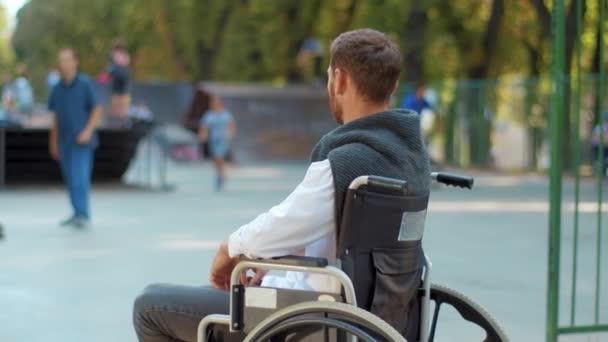 Erschossener depressiver Mann, der im Rollstuhl auf Spielplatz im Park sitzt, ist traurig. Gelähmte Krankheit Gesundheitsversorgung Verzweiflung Beeinträchtigung. Zeitlupe