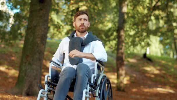 Schwerwiegender junger Mann im Rollstuhl beim Zigarettenrauchen im schönen Park bei Sonnenlicht. Gehbehinderung bärtig hübsch. Porträt. Zeitlupe