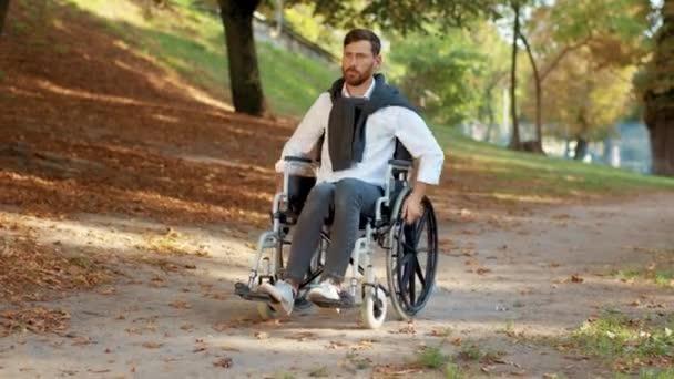 Junger Mann im Rollstuhl fährt im Park bei Sonnenlicht. Behinderte mit Lähmungen. Ernsthaft. Draußen Herbst. Zeitlupe