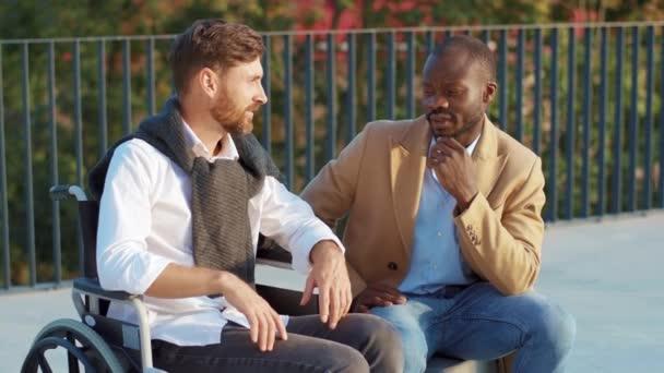 Gesicht glücklicher Mann im Rollstuhl mit afrikanisch-amerikanischen Freund Blick in Kamera lächeln im Herbst Park. Unterstützen Sie attraktive Walking Transport Gesundheit Medizin zusammen. Zeitlupe