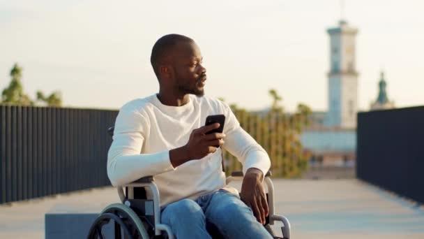 Schwerwiegender junger behinderter Mann benutzt Handy im Rollstuhl in einem Park und schaut sich draußen im Sonnenlicht um. Behindertenzellen nennen Behinderte Verletzungen im Sitzen Gesundheitsversorgung. Zeitlupe