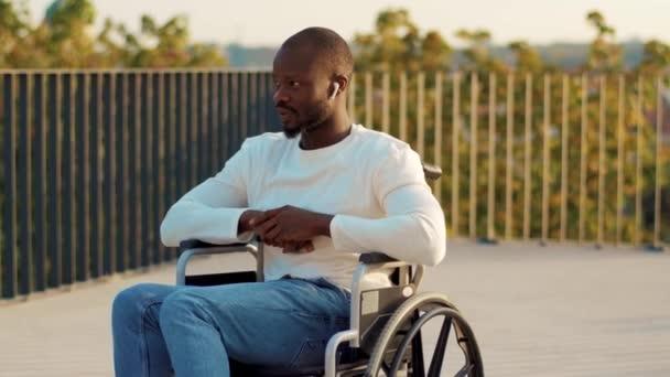 Entspannter junger Mann hört Musik über Kopfhörer auf einem Rollstuhl in einem Park und schaut sich draußen im Sonnenlicht um. Behindertenzellen nennen Behinderte Verletzungen im Sitzen Gesundheitsversorgung. Zeitlupe