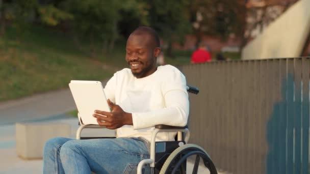 Attraktiver junger afrikanisch-amerikanischer Mann im Rollstuhl mit Tablet-Computer im Park bei Sonnenlicht Behinderung Medizin. Möglichkeit behinderte Behinderte Internet. Zeitlupe