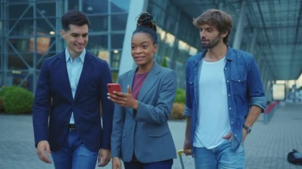 Cheerful corporate team of successful young multi-ethnic business people sharing smartphone screen discussing great news about their company. Staff. Business. Outdoors.