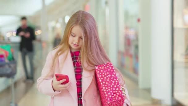 Šťastná usměvavá dívka chodit v nákupním středisku s vánoční dárek krabice použít telefon dítě rodina atraktivní teenager krásné děti veselé štěstí dovolená dítě usmívá dětství zpomalený film