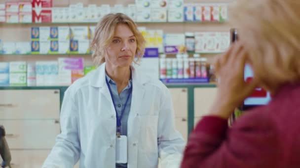 Eine junge Apothekerin bedient eine Kundin in einem Drogeriemarkt. Gespräch mit dem Kunden. Verkäufer kommerziellen gesundheitspflege käufer uniform. Zeitlupe