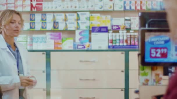 Attractive woman pharmacist serving a customer in a drugstore. Conversation pharmaceutical client. Seller commercial health care buyer uniform. Slow motion