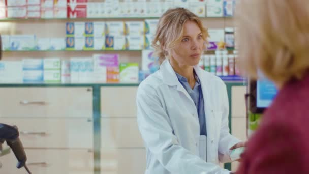 Apothekerin in Großaufnahme, die eine Kundin in einem Drogeriemarkt bedient. Gespräch mit dem Kunden. Verkäufer kommerziellen gesundheitspflege käufer uniform. Zeitlupe