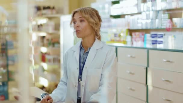 Slow motion woman pharmacist serving a customer in a drugstore. Conversation pharmaceutical client. Seller commercial health care buyer uniform.