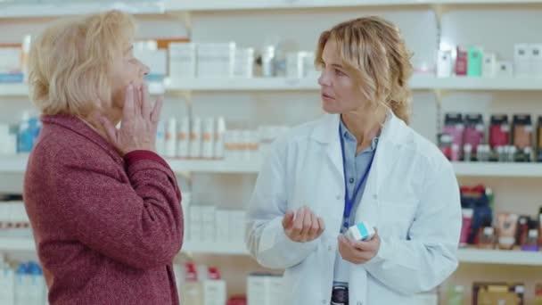 In einer Apotheke bedient eine Apothekerin eine Kundin. Gespräch mit dem Kunden. Verkäufer kommerziellen gesundheitspflege käufer uniform. Zeitlupe