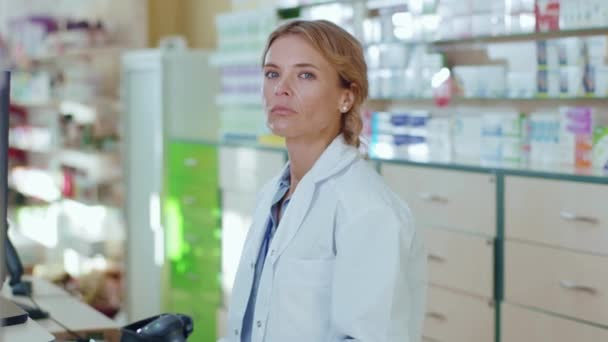 Tired young woman in uniform pharmacist at pharmacy stand look at camera serious. Diagnosis young pharmaceutics store job healthy medicine. Slow motion