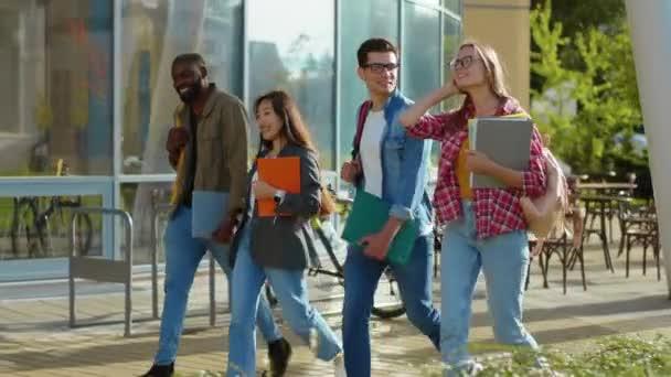Čtyři různorodí pohlední mladí lidé procházející se po ulici. Skupina chytrých atraktivních multietnických studentů, kteří chodí na univerzitu. Koncept vzdělávání a lidí. Přátelství.