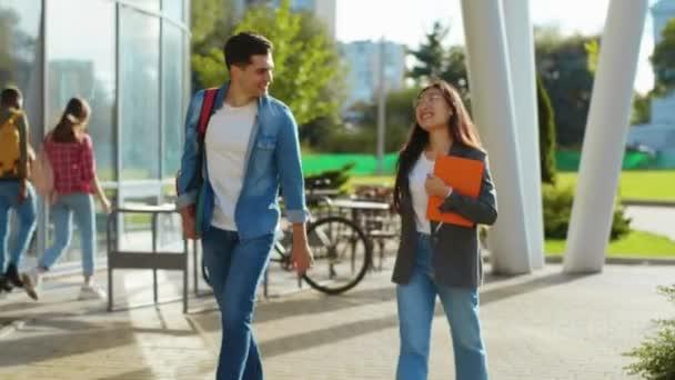 Míšenec-závod krásné mladé legrační pár studentů procházky po ulici v časných ranních hodinách mluvení před vyučováním. Chytrá generace. Přátelství. Komunikace.