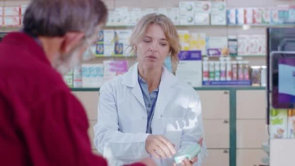 Bei Sonnenlicht bedient eine Apothekerin eine Kundin in einem Drogeriemarkt. Gespräch mit dem Kunden. Verkäufer kommerziellen gesundheitspflege käufer uniform. Zeitlupe