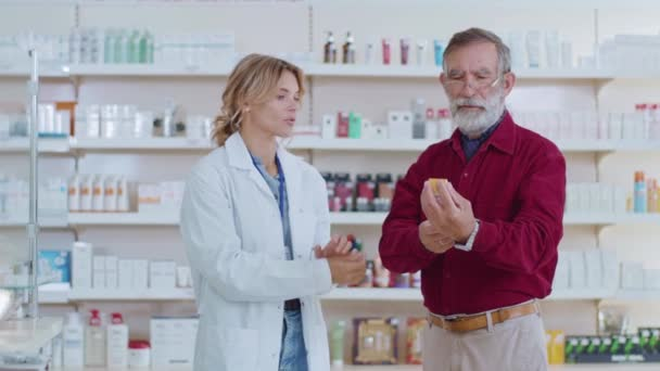 In pharmacy woman pharmacist serving old man customer drugstore. Conversation pharmaceutical client. Seller commercial health care buyer uniform. Slow motion