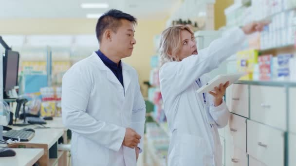 Serious woman and Asian man cooperating in drugstore use tablet computer. Attracitve woman apothecarist talking with male colleague learning pills. Slow motion