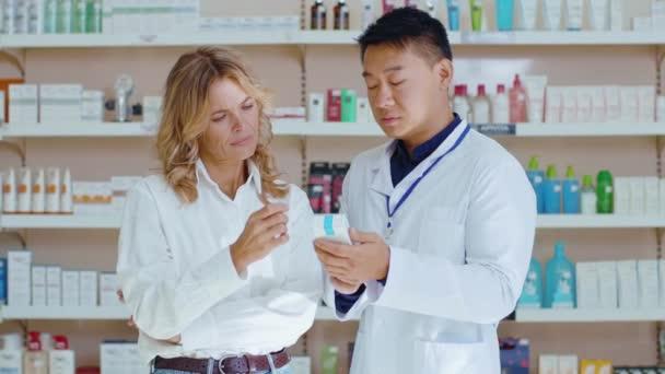 Porträt eines asiatischen Mannes professioneller Pharmazeut im Gespräch mit einem Kunden, der in einer modernen Drogerie arbeitet. Apotheke, Medizin, Berufskonzept. Zeitlupe