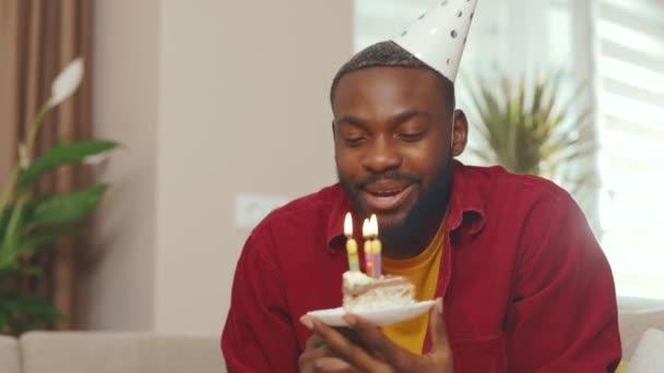 Ein hübscher afroamerikanischer junger Mann, der seinen Laptop zum Videoanruf benutzt, um online Geburtstag zu feiern, bläst während der Quarantäne Kerzen auf dem Kuchen aus. Distanzierung Kommunikationsnetzwerk sozialen. Zeitlupe