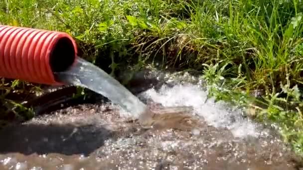 Wasser aus einem roten Wellrohr fließt den Abfluss hinunter. Wasser fließt. Regenwasser fließt aus dem Rohr und fällt herunter. Abwasser fließt in den externen Kanal. Wasser mit einer Pumpe pumpen