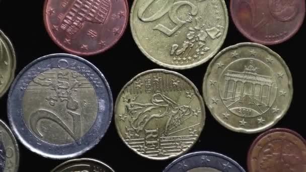 Eurocentes érmék egy fekete háttér forog közelkép. A fény és a forgás játéka. Makró lövés. Lapos fekvés. A pénzügyi válság és csőd fogalma a koronavírus-járvány idején.