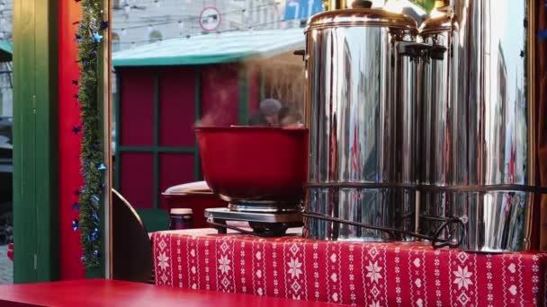 Draußen am Feuer gekochter Glühwein. Straßenfest auf dem Weihnachtsmarkt im Winter. Heißer Glühwein. Dichter Dampf über Glühweinkesseln. Menschen im Hintergrund. Ukraine, Kiew - 07. Januar 2020.