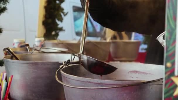 Glühwein kochen auf einem Straßenfest in Metallkesseln. Ein heißes alkoholisches Getränk aus Wein, Gewürzen und Früchten. Heißer Dampf verdunstet aus der Pfanne. Konzept von Weihnachten, Urlaub, Advent, Trinken