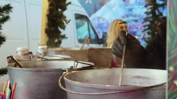 Glühweinverkauf auf einem Straßenfest in Metallkesseln. Der Verkäufer schenkt dem Käufer ein Glas heißes alkoholisches Getränk aus Wein, Gewürzen und Früchten ein. Weihnachts- und Feiertagskonzept