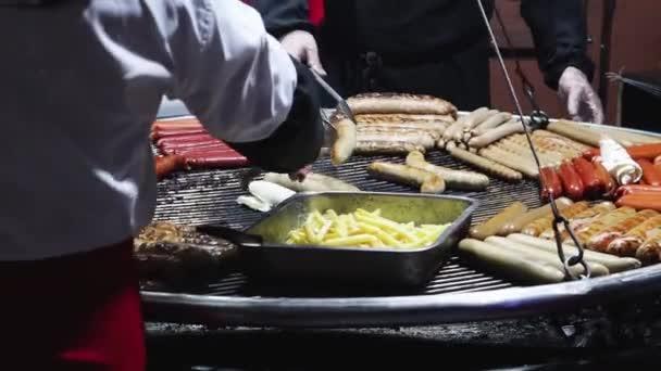Grilované klobásy a hranolky na velkém kovovém stojanu na slavnostním večerním trhu. Pouliční jídlo, fast food, tuk. Vánoční a novoroční veletrhy - prodejci rychlého občerstvení