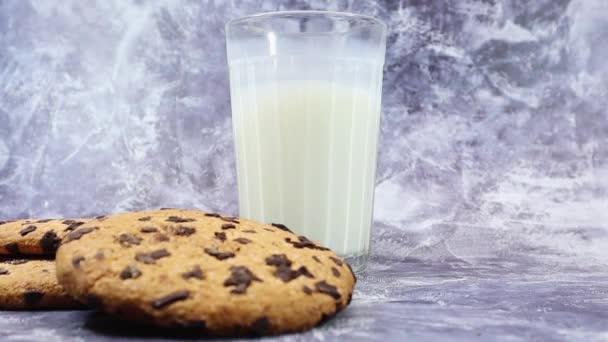 Americké čokoládové sušenky a mléko ve sklenici na pozadí na šedém pozadí. Tradiční kulaté křupavé těsto s čokoládovými lupínky. Pekárna. Lahodný dezert, pečivo