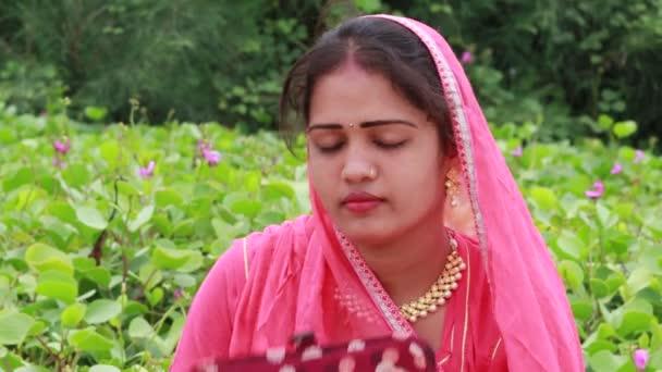 Eine schöne junge indische Frau sitzt in einem grünen Garten und färbt ihre Augenbrauen mit schwarzer Farbe. Ein Model trug gemäß ihrer Sitten und Kultur traditionell ein rosafarbenes Kopftuch (dupatta)