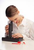 young female student using microscope in science laboratory