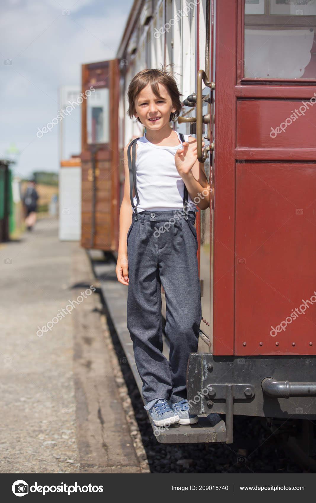 1be4fa93d2b0 Όμορφο παιδί, ντυμένοι με ρούχα vintage, απολαμβάνοντας το παλιό ατμοκίνητο  τρένο μια καυτή θερινή ημέρα στην Αγγλία — Εικόνα από ...