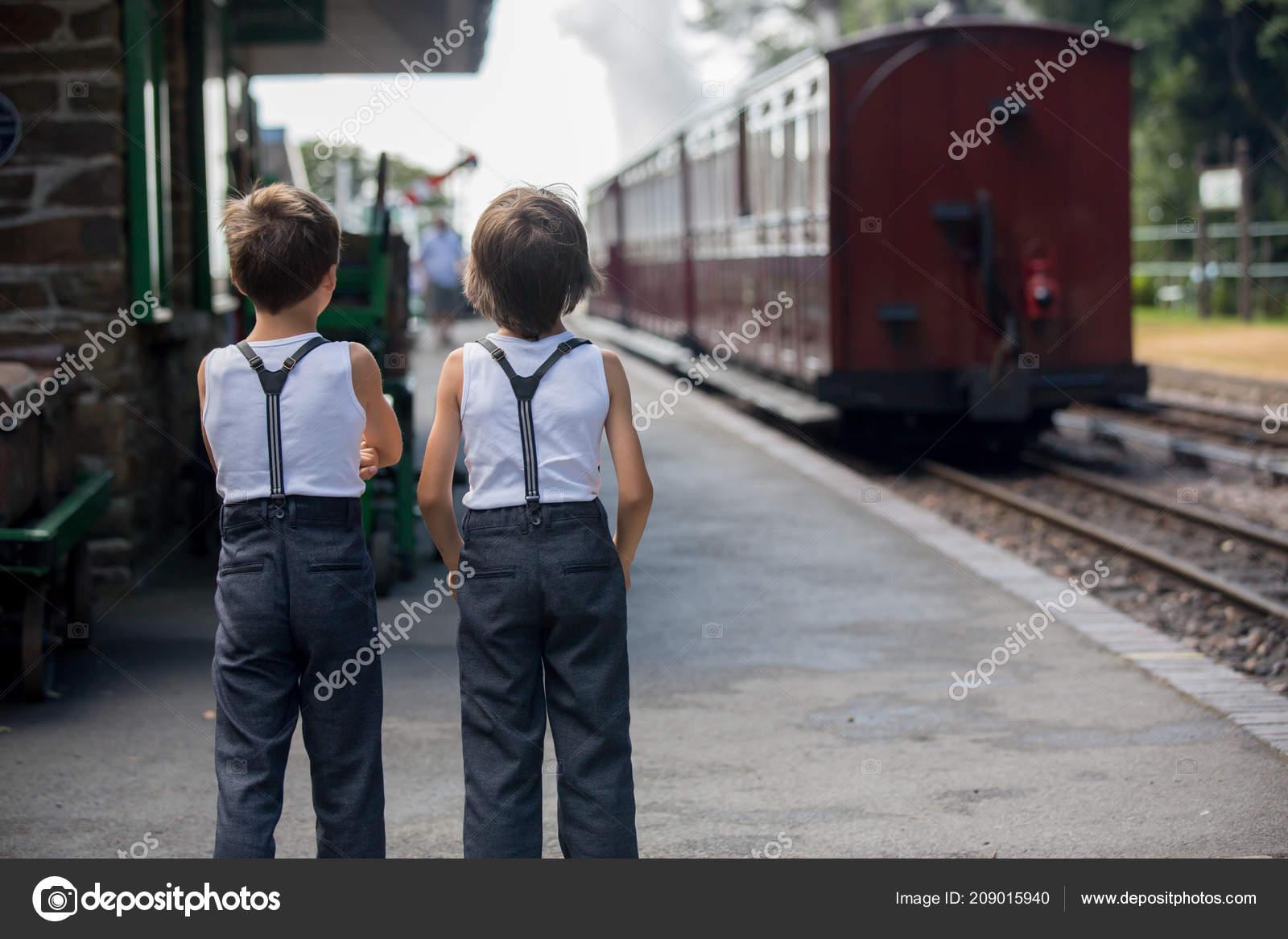 5ab9dab519a2 Όμορφα παιδιά, ντυμένοι με ρούχα vintage, απολαμβάνοντας το παλιό  ατμοκίνητο τρένο μια καυτή θερινή ημέρα στην Αγγλία — Εικόνα από  t.tomsickova