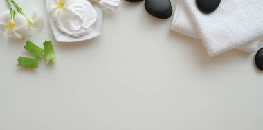 Top view of black stones and towels for massages on white backgr
