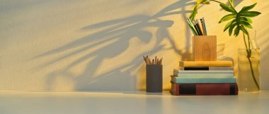 Close up view of study table with copy space, stationery, books, elements and plant vase in home office room