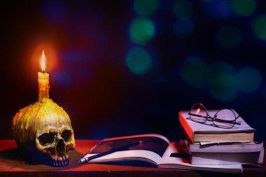 Still life image of wizard wooden desk with skull of lighting ca