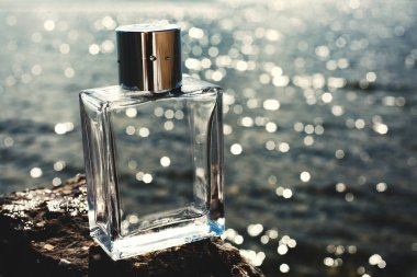 male perfume on sea background at sunset