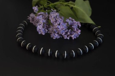 Bright black beads with a white stripe and lilac with green leav